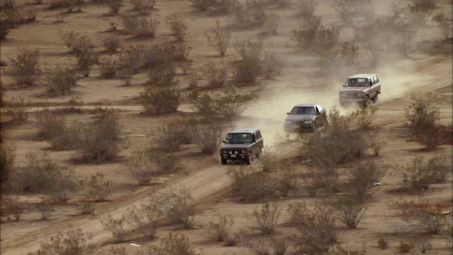 three vehicles drive on a dusty desert road. - convoy stock videos & royalty-free footage