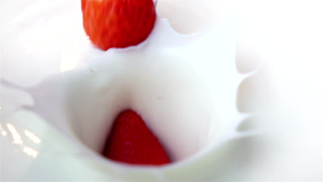 Three videos of strawberries falling into yogurt -real slow motion