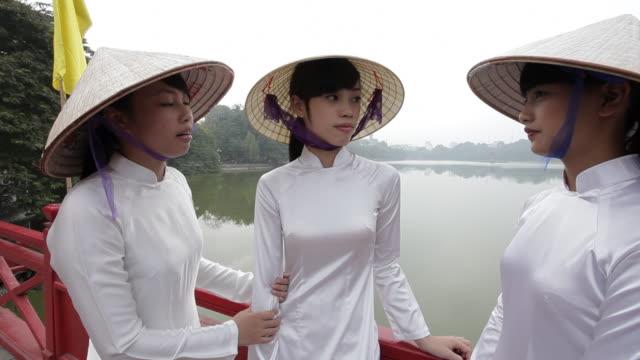 Three Vietnamese women in traditional dress visit on the shore of Ho Kiem Lake in Hanoi, Vietnam.