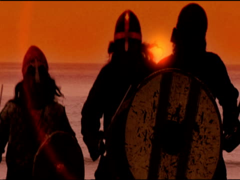three viking men run towards camera holding up shields and swords under orange sky - viking stock videos and b-roll footage