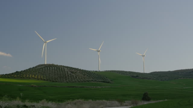 vídeos y material grabado en eventos de stock de ms three wind turbines on crest of green hill, red r3d 4k - temas sociales