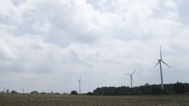 three wind turbines rotate in wind - three objects stock videos & royalty-free footage