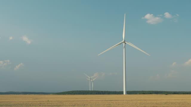 vídeos y material grabado en eventos de stock de three wind turbines spinning in a wheat field in day time - trigo
