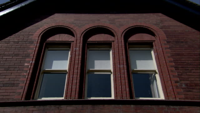 three windows framed by arches are set side by side on a brick house. available in hd. - brick house stock videos and b-roll footage