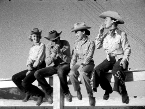 Three women amp man dressed in Western clothing amp cowboy hats sitting on corral fence male lighting cigarettes female then self all looking left...