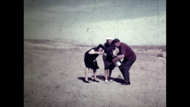 three women and one man drinking water from tin can in the middle of nowhere; windy day - grand canyon stock videos & royalty-free footage