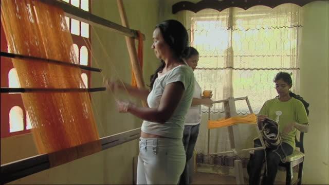 vídeos de stock e filmes b-roll de ms three women at looms with orange yarn / colombia - mill