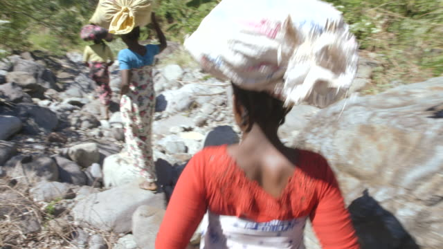 Three women balance sacks of ylang-ylang flowers on their head as they walk down a rocky valley on the island of Anjouan.