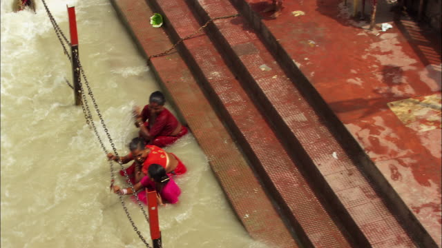 Three women cool off in the Ganges River in India. Available in HD.