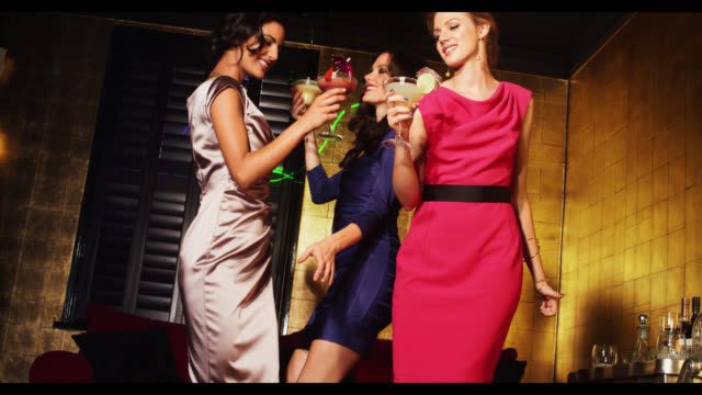 three women dacing with cocktail drinks - gold dress stock videos & royalty-free footage