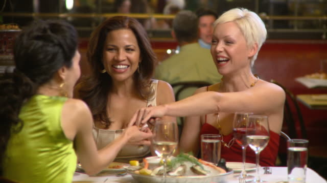 MS Three women dining at upscale restaurant, celebrating engagement, admiring ring, Richmond, Virginia, USA