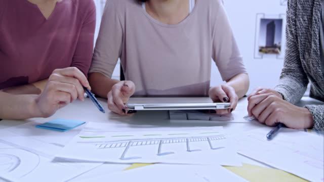 Drei Frauen, die Diskussion über die design-Entwurf vor Ihnen
