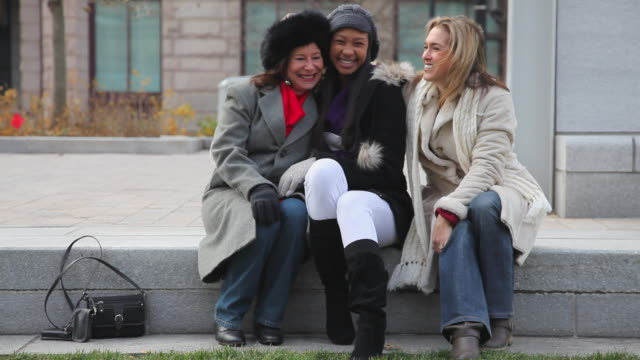 Three women friends smile into the camera as they sit outside on a step.