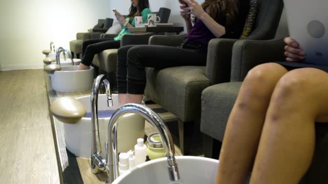 three women getting a pedicure in a spa - 自己改善点の映像素材/bロール