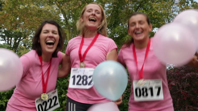 Three women in 40's after charity run. With pink shirts runner numbers and blue and pink balloons