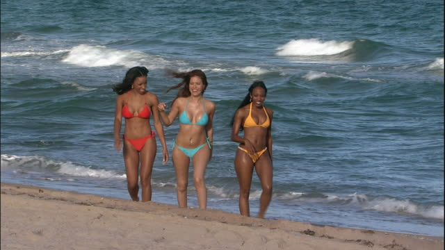 vídeos de stock, filmes e b-roll de three women in bikinis walk together on a beach. - biquíni
