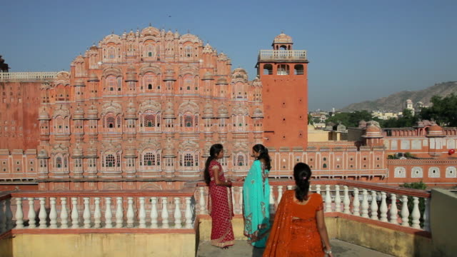 Three women in colorful saris visit on a balcony near Palace of the Winds in Jaipur, India.