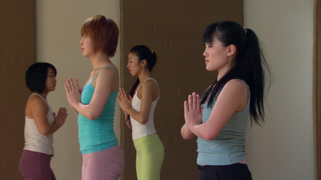 ms zo three women in yoga class standing with eyes closed and hands together as instructor speaks/ new york, nye - squatting position stock videos & royalty-free footage