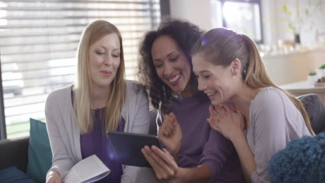 three women laughing at something on a digital tablet - only young women stock videos & royalty-free footage