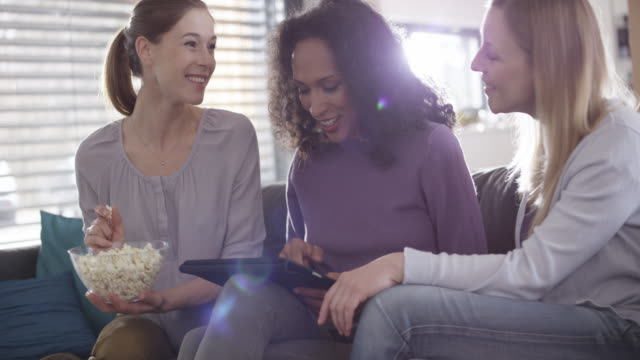three women laughing while scrolling on a digital tablet - only young women stock videos & royalty-free footage