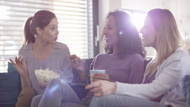 three women laughing while watching tv and eating popcorn - guardare la tv video stock e b–roll