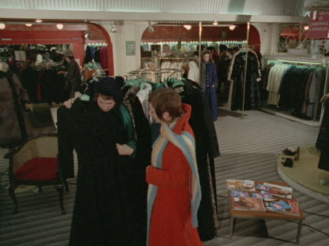 stockvideo's en b-roll-footage met three women look at maxicoats in a boutique - kleding