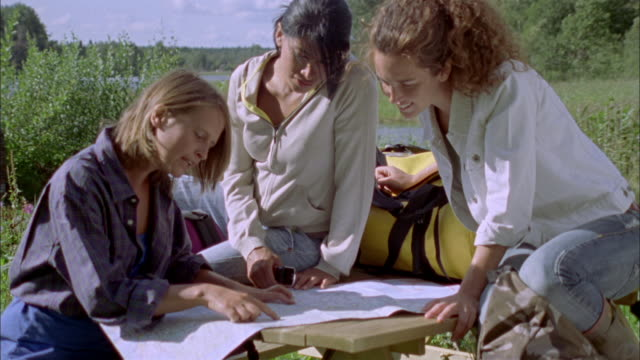 MS Three women looking at map sitting on picnic table, Ryd, Smaland, Sweden