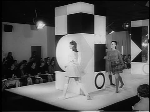 b/w 1966 three women modeling kilts marching on runway indoors / london / newsreel - 1966年点の映像素材/bロール