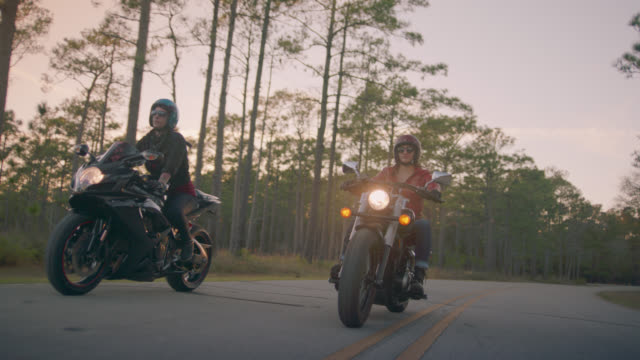 slo mo. three women on motorcycles cruise down secluded two lane blacktop. - motorradfahrer stock-videos und b-roll-filmmaterial