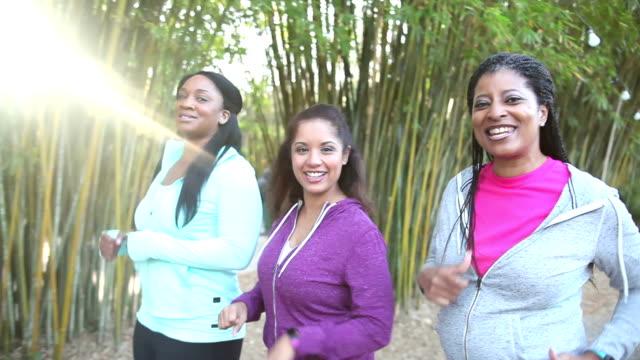 vídeos y material grabado en eventos de stock de poder de tres mujeres caminando en el parque hablando con cámara - pedestrismo