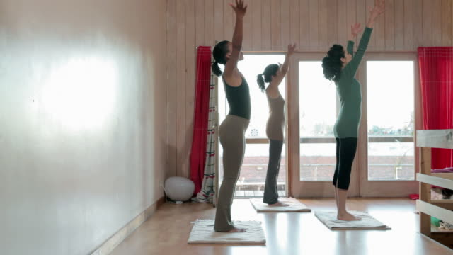 three women practicing yoga - sun salutation stock videos and b-roll footage