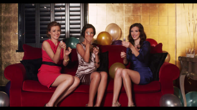 Three women pull party poppers