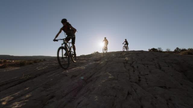vídeos y material grabado en eventos de stock de three women ride mountain bikes down rocky trail in moab. - mountain bike