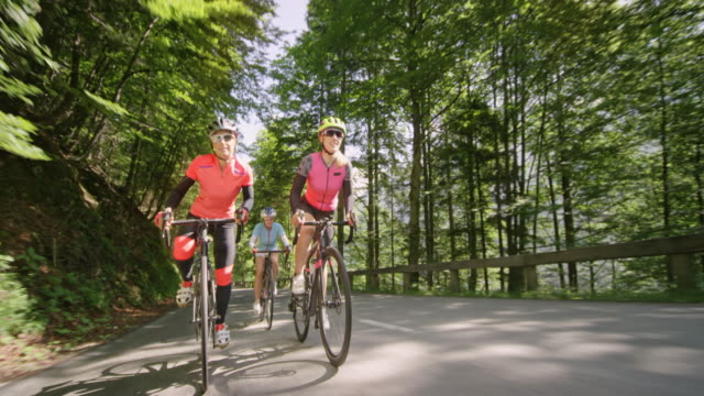 three women riding their road bikes down an asphalt mountain road on a sunny day - females stock videos & royalty-free footage