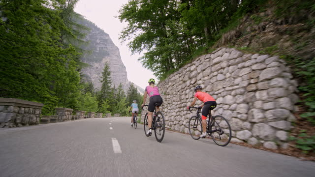 three women riding their road bikes on a mountain road - bicycle trail outdoor sports stock videos & royalty-free footage
