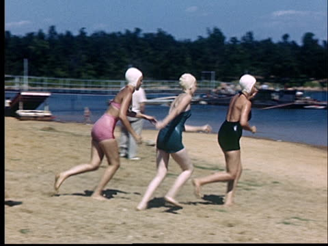 ws, pan, three women running into lake, 1950's, oklahoma, usa - swimming cap stock videos and b-roll footage