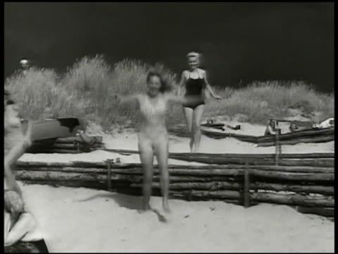vídeos y material grabado en eventos de stock de three women running to beach from dunes ws people sitting on beach w/ dunes bg young adult women talking sunbathing on beach wwii active neutrality... - recostarse