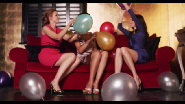 Three women sat playing with balloons