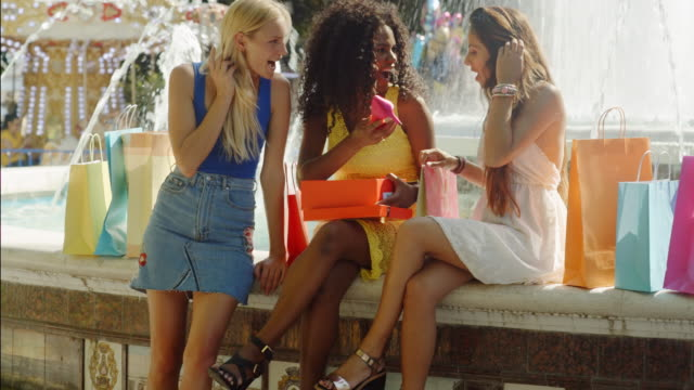 Three women sitting by fountain looking at new shoes
