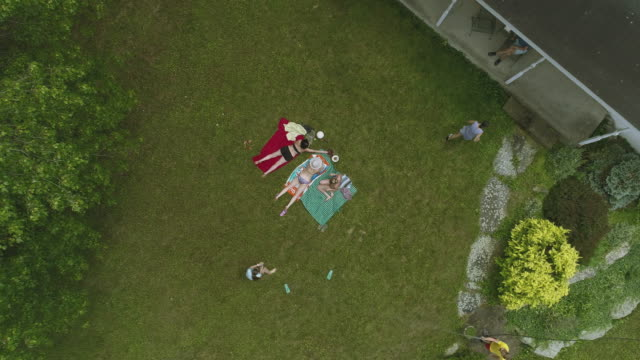 Three women sunbathing on the lawn, and kids playing with water around. Top view directly above, aerial drone video