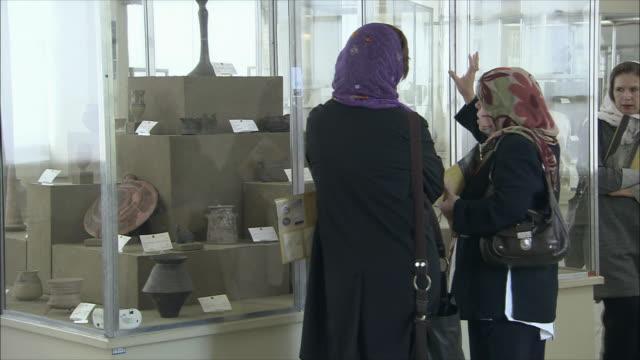 ms pan three women talking in front of cabinet in national museum of iran, tehran, iran - skåp med glasdörrar bildbanksvideor och videomaterial från bakom kulisserna