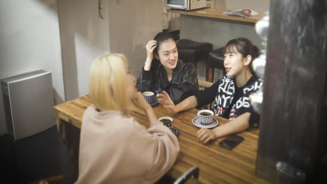 three women talking while drinking coffee - 3人点の映像素材/bロール