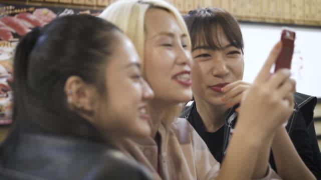 three women talking while watching smartphone - 親睦会点の映像素材/bロール