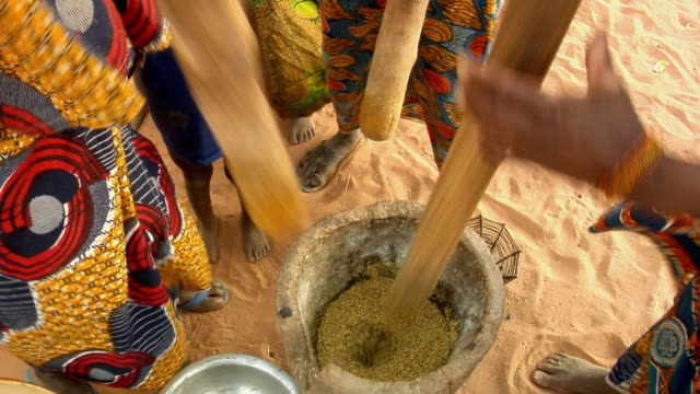 ha, cu, three women using mortar and pestle for grinding millet grain, low section, niamey, niger - ニアメ点の映像素材/bロール