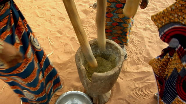 ha, cu, three women using mortar and pestle for grinding millet grain, low section, niamey, niger - ニジェール点の映像素材/bロール