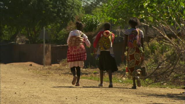 vídeos de stock e filmes b-roll de three women walk along a dirt road in a village in malawi.  - malávi
