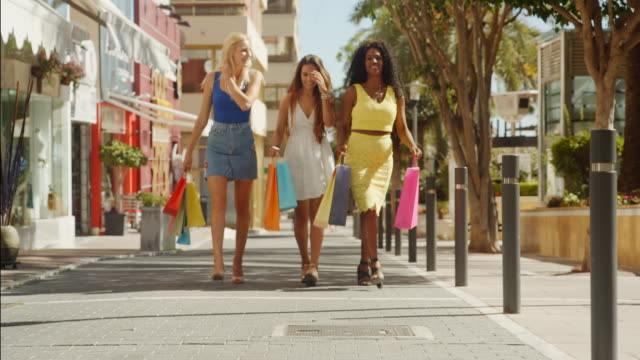 three women walking towards camera with shopping bags in town - tragetasche oder tragebeutel stock-videos und b-roll-filmmaterial