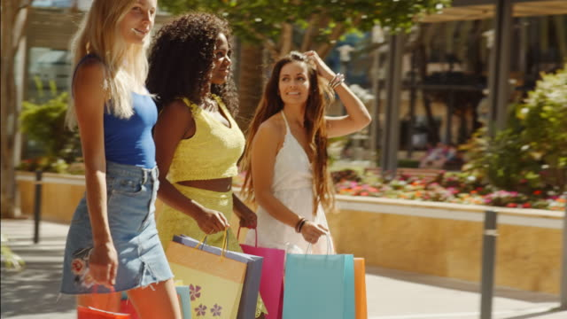 Three women walking with shopping bags in town