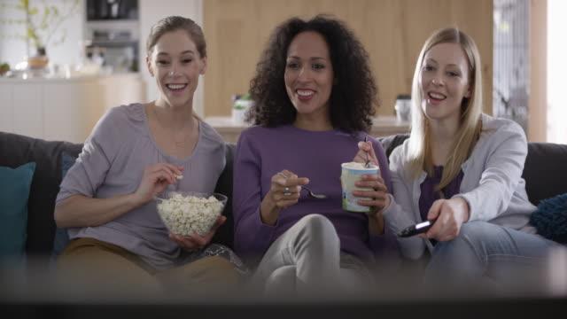 Three women watching TV and having fun