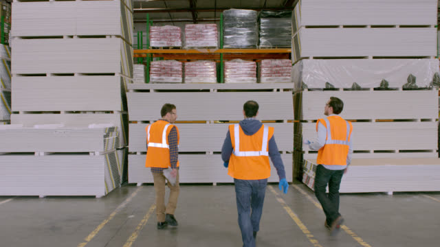 Three workers entering frame from behind camera, walking to stacked goods in warehouse